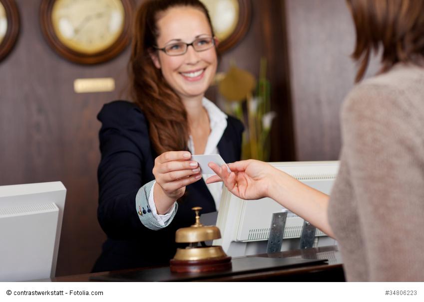 rezeptionistin überreicht einem gast die karte
