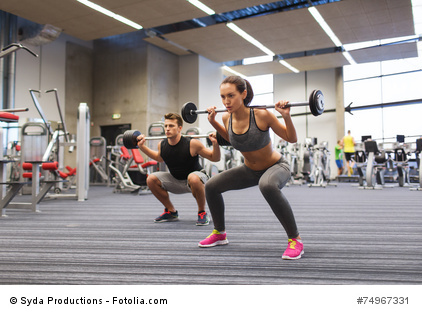young man and woman training with barbell in gym